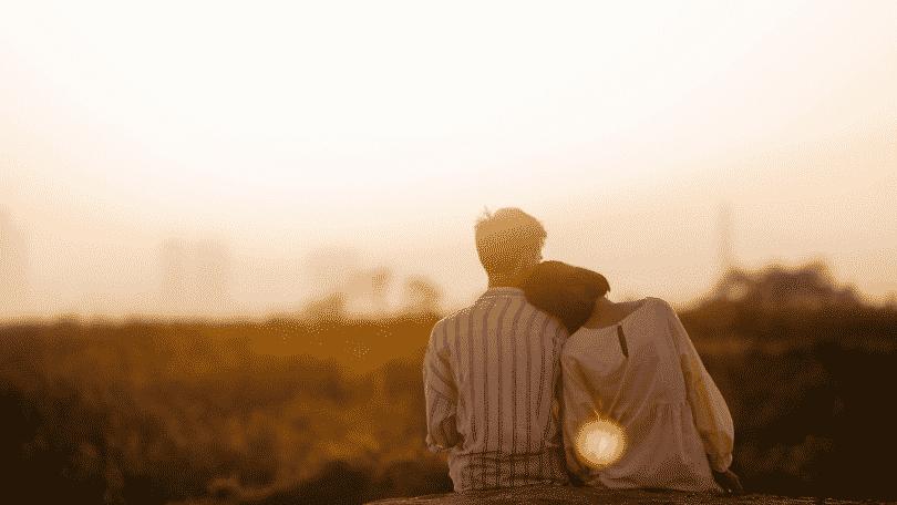 Casal sentados olhando o pôr-do-sol