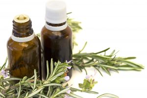 Essential aroma oil with rosemary on white background. Selective focus.