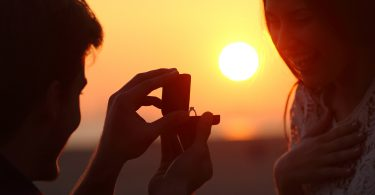Back light of a couple proposal of marriage on the beach at sunset ** Note: Shallow depth of field