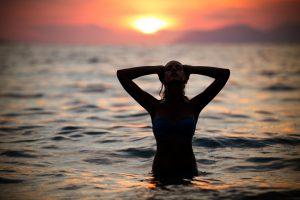 Gorgeous sexy fit woman silhouette swimming in sunset.Free happy woman enjoying sunset. Beautiful woman in water embracing the golden sunshine glow of sunset, enjoying peace, serenity in nature.