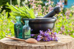 Black Mortar With Sage Herbs, Glass Bottles Of Essential Oil Out
