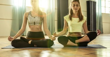 couple of girls making yoga in the gym. both of them sitting on the floor and relaxing in yoga position