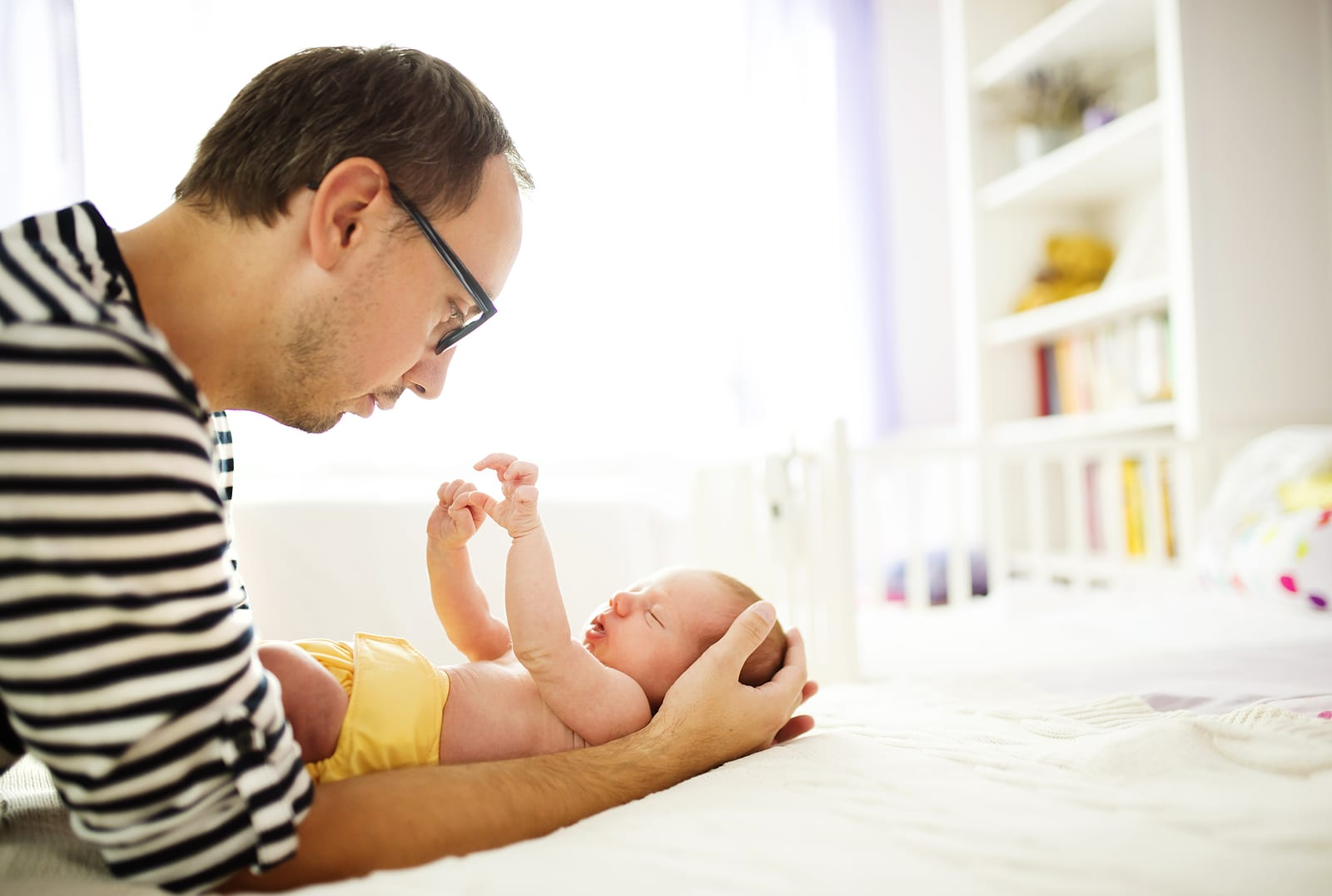 Happy young father enjoying special moments with his newborn baby daughter at home