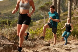 Fit young people running up a hill. Trail running training. Young and fit athletes running cross country.