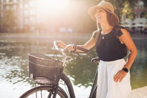Portrait of beautiful young woman wearing a hat with a bicycle walking along a pond. Happy woman with a bike at the park looking away laughing on a summer day with sun flare.