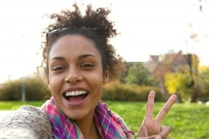 Selfie portrait of a happy young woman with peace sign