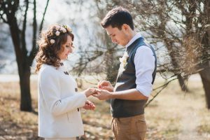 Bride and groom exchanging wedding rings. Wedding couple. People in love. Young man and beautiful woman in spring park. Marriage proposal. Outdoors wedding ceremony. Happy people