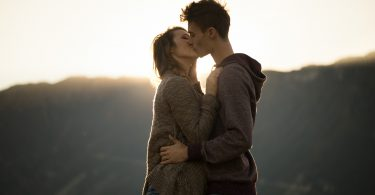 Romantic young couple kissing passionately at sunset mountains on background feelings and relationships concept