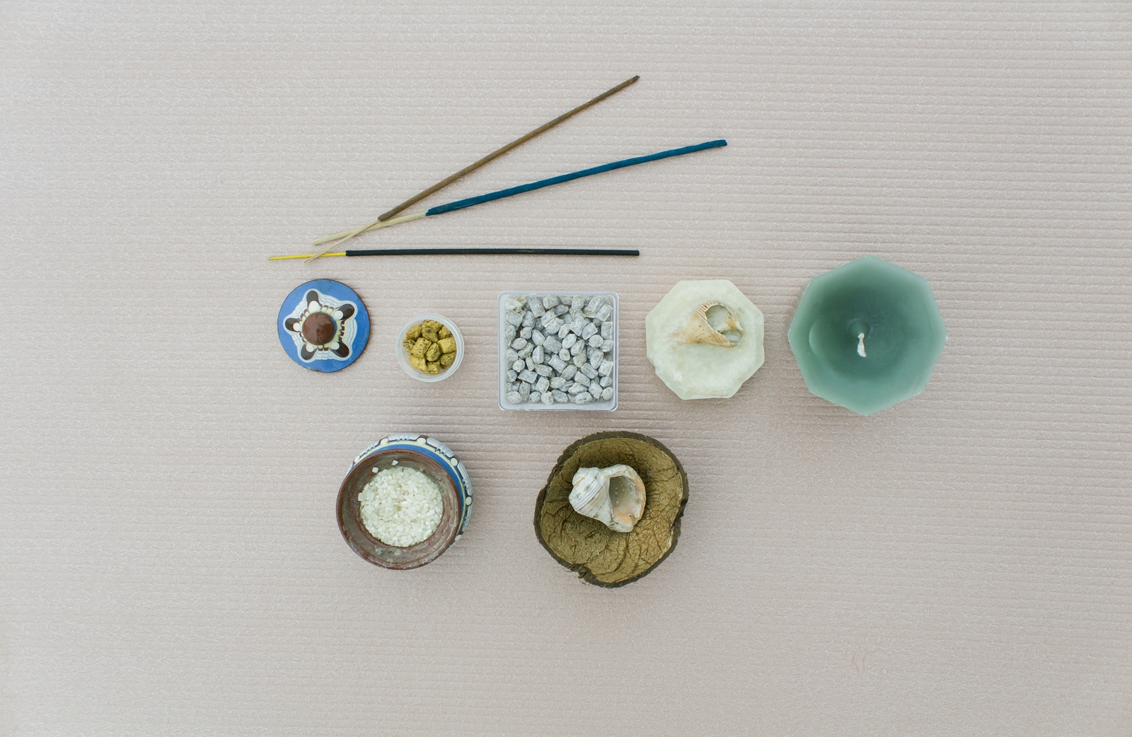 The composition of the components of a meditation on light beige background. Church and Indian incense and incense candles and shells a pot of rice as a stand rod.