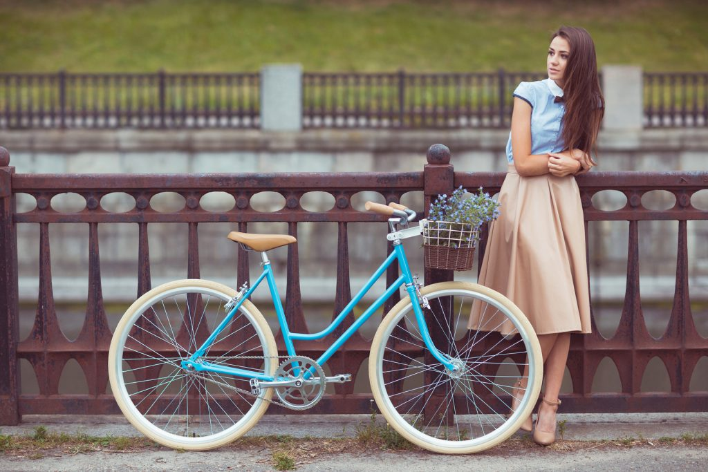 Young beautiful elegantly dressed woman with bicycle. Beauty fashion and lifestyle [[** Note: Shallow depth of field ** Note: Visible grain at 100%, best at smaller sizes