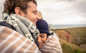 Young couple laughing outdoors under blanket in a cold day