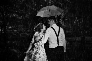 Young romantic couple in love flirting in rain, man holding umbr