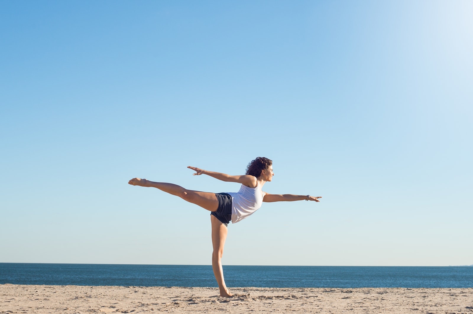 Young woman performing yoga on the beach during a beautiful morn