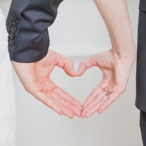 wedding couple showing shape of heart from their hands. single whole from man and woman. Wedding couple forming heart shape. wedding couple hands touching fingers in the shape of hearts.