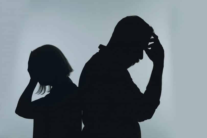 Silhueta de casal brigado. Um está de trás para o outro e com uma mão sobre os rostos, além de estarem cabisbaixos.