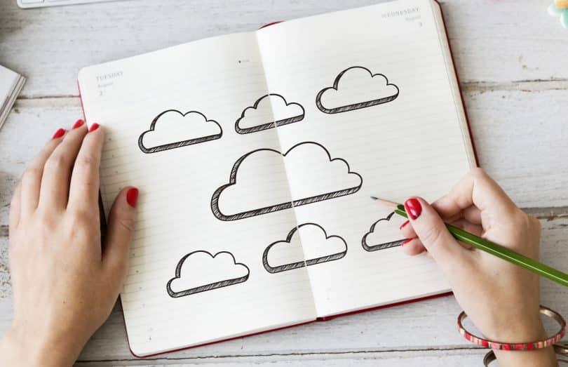 Pessoa desenhando nuvens em um caderno.