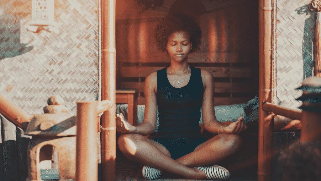 Mulher meditando de olhos fechados na fachada
