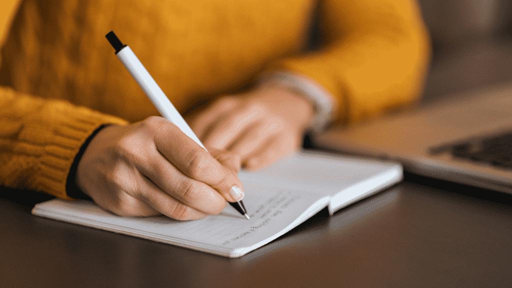 Mulher anotando em seu bloco de notas