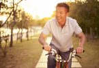 mid-adult asian man riding bicycle outdoors in a park at sunset, smiling and happy, concepts for fitness, sport and exercise, healthy life and lifestyle.
