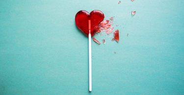 Broken heart lollipop on a green background