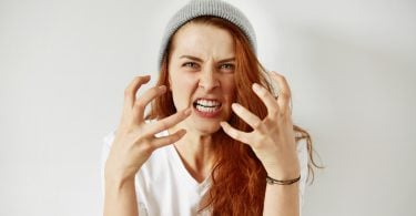 Close up isolated portrait of young annoyed angry woman holding hands in furious gesture. Young female with red hair in white T-shirt and cap. Negative human emotions face expressions. Film effect