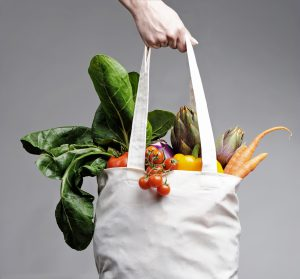 full of vegatables cotton shopping bag carried by a human hand