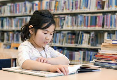 Cute Little Girl Reading Books at Library Corner