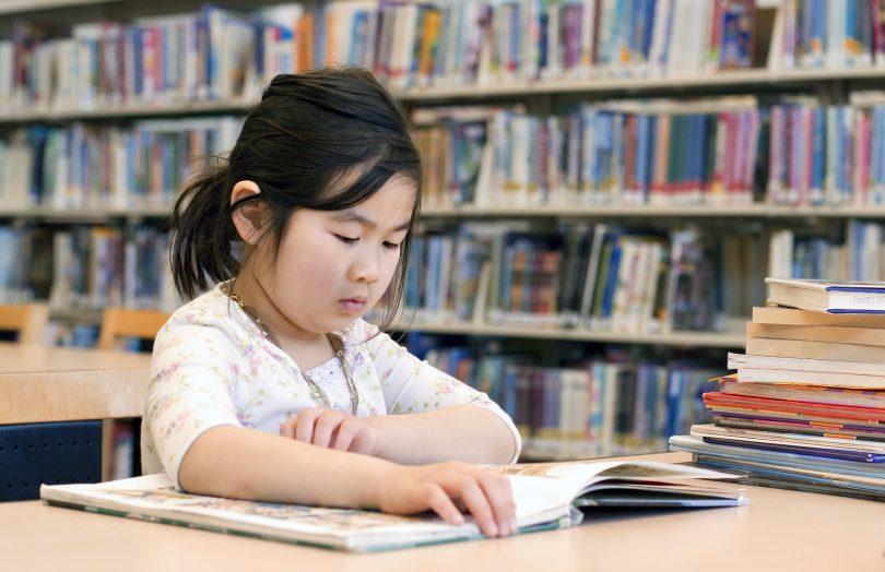 Cute Little Girl Reading Books at Library Corner