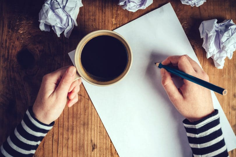 Mãos sobre uma mesa segurando café e escrevendo em um papel sulfite