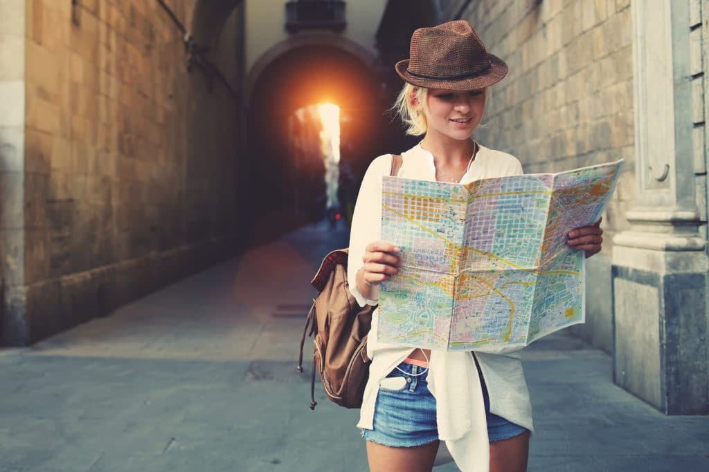 Cheerful woman wanderer with trendy look searching direction on location map while traveling abroad in summer