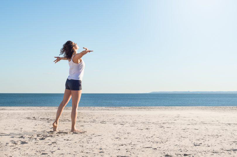 Mulher na praia com braços abertos olhando para o mar