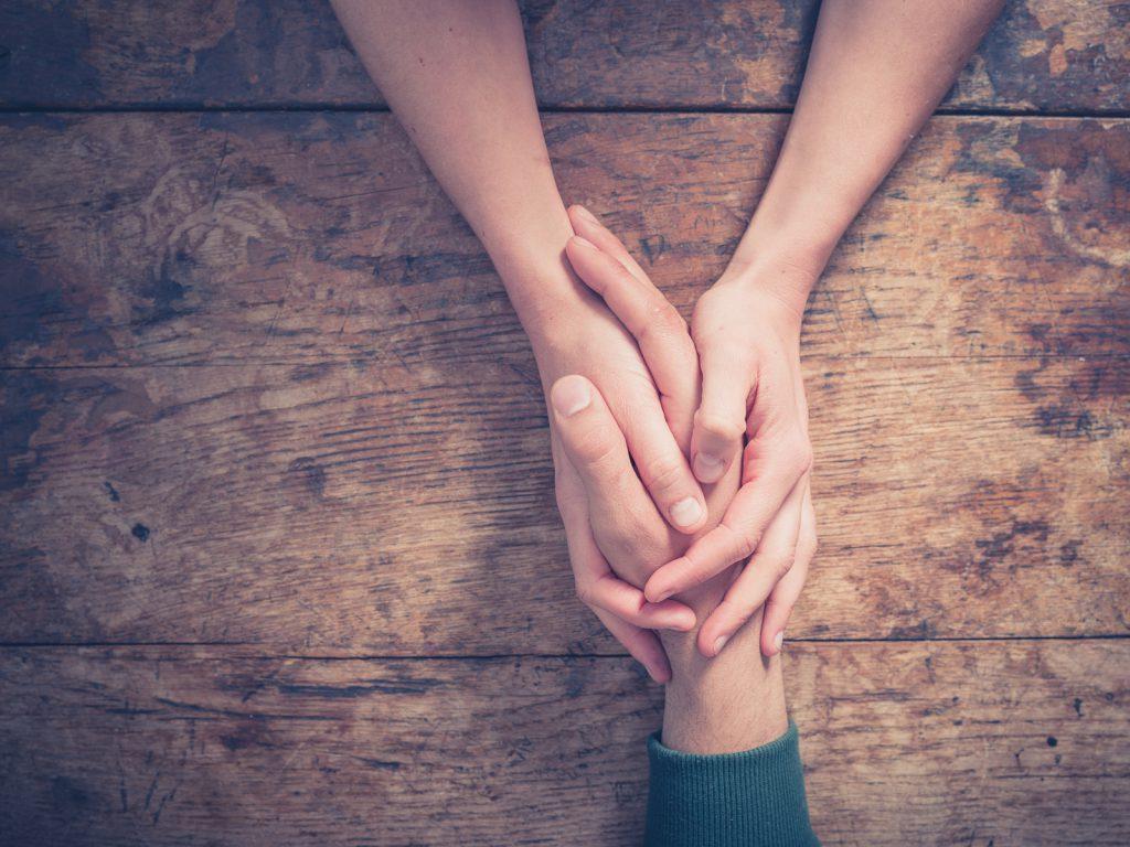 Duas pessoas segurando as mãos uma da outra em cima de uma mesa de madeira.