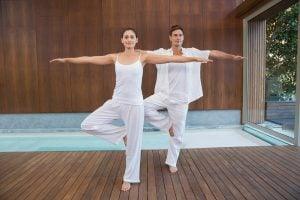 Peaceful couple in white doing yoga together in tree position in