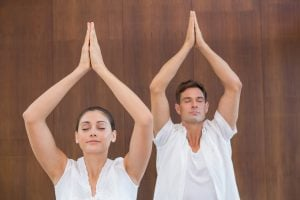 Peaceful couple in white doing yoga together with hands raised i