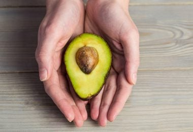 Woman showing fresh avocado in close up
