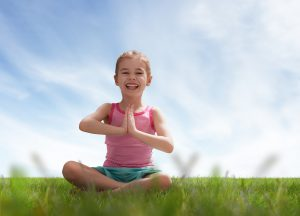 child practicing yoga on the grass outdoors