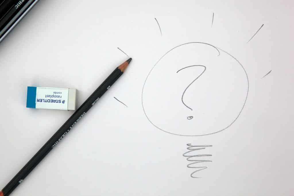 Sinal de interrogação escrito em papel com um lápis.