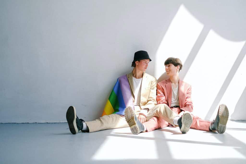 Dois homens sentados no chão suando roupas sociais coloridas um olhando para o outro