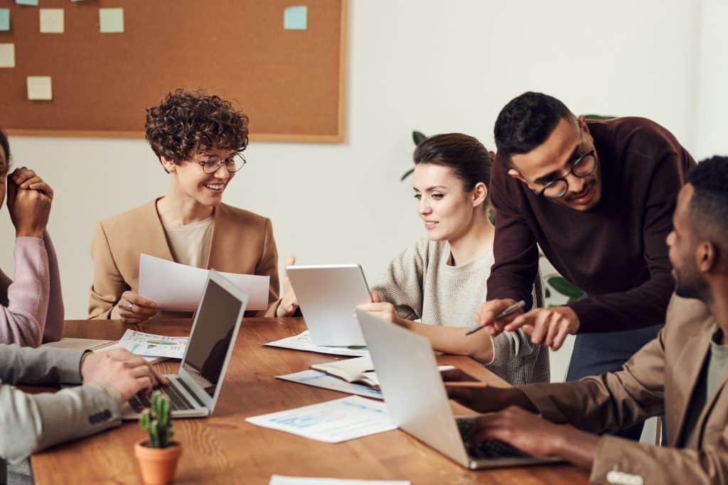 Mulheres na mesa do escritório sorrindo ao lado de homens