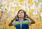 Criança em um parque de olhos fechados segurando seu fone de ouvido