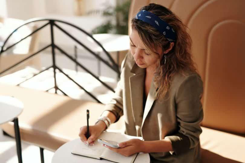 Mulher escrevendo em um caderno em um escritório