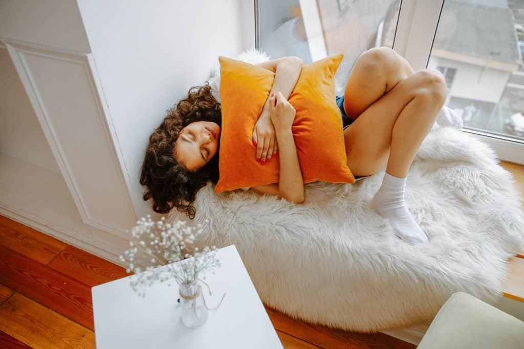 Mulher deitada abraçada em uma almofada
