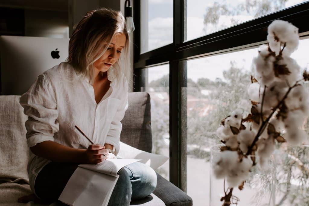 Mulher sentada em uma poltrona ao lado da janela, escrevendo em um caderno.