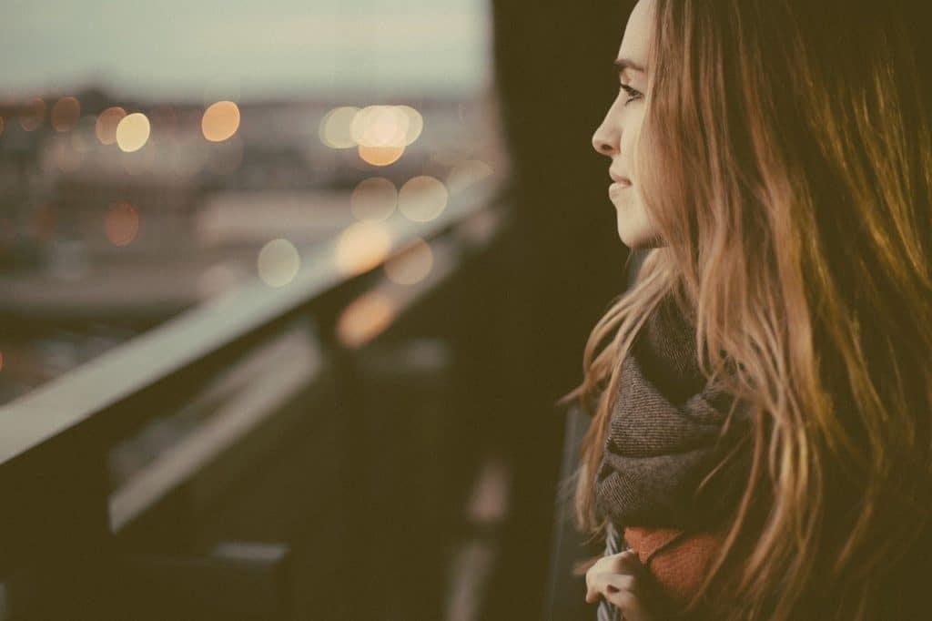 Mulher de perfil olhando para a paisagem da cidade ao seu lado.