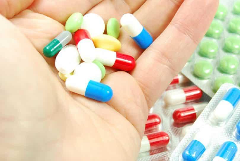 Medicamentos sobre palma de uma mão. Ao fundo, há cartelas fechadas com mais pílulas.
