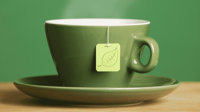 Xícara verde com chá quente