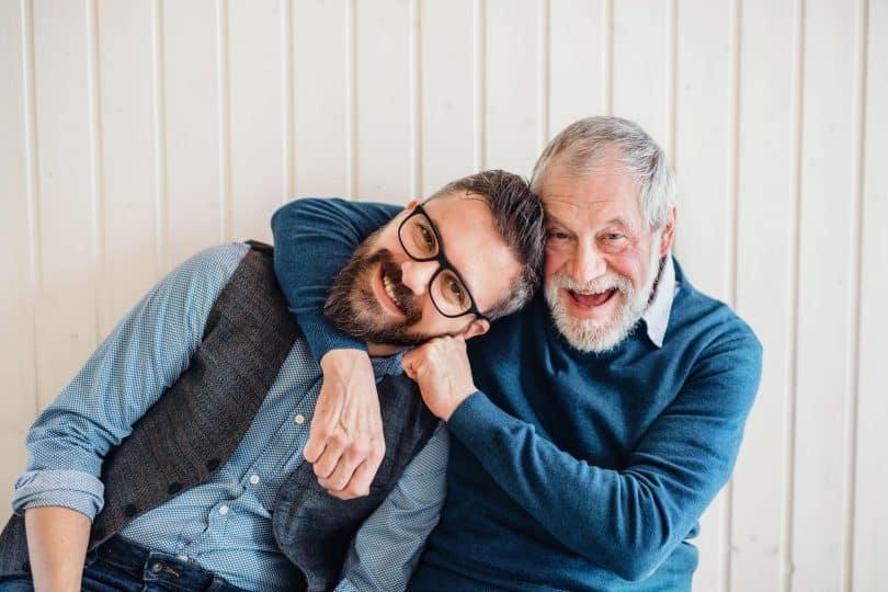 Homens braços abraçados, com expressões sorridentes.