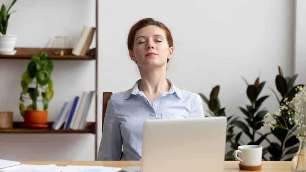 Mulher em seu escritório de olhos fechados e respirando profundamente