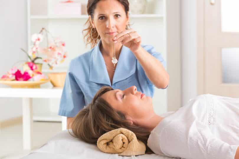 Mulher segurando pêndulo em cima de mulher deitada de olhos fechados