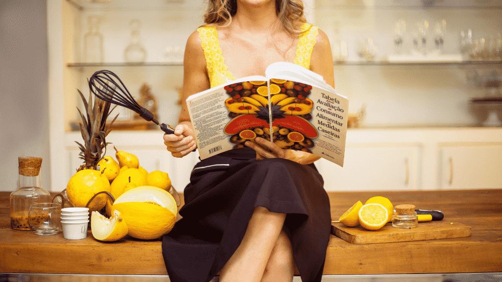 Mulher sentada na mesa da cozinha com livro de receita em mãos